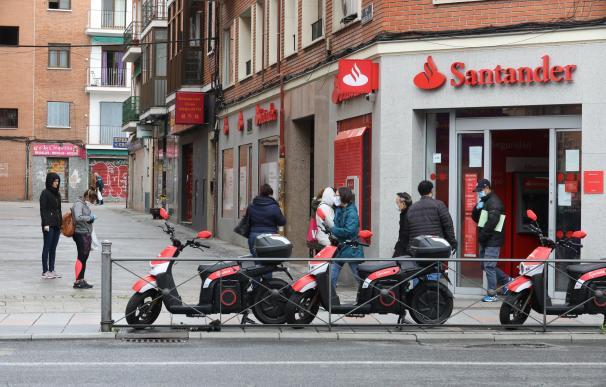 Varias personas esperan para entrar a una oficina del Banco Santander durante el inicio de la cuarta semana del estado de alarma decretado a consecuencia del coronavirus