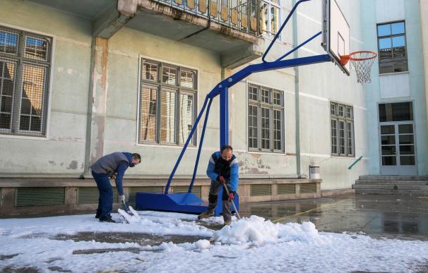Personal de mantenimiento del Colegio Escuelas Pías de Zaragoza se afana en limpiar la nieve que cubre el patio de recreo del centro este martes.