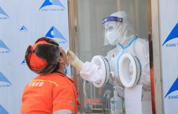 Un sanitario chino es sometido a una prueba de coronavirus en Pekín.