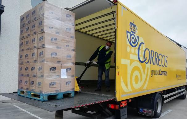 Imagen de un camión de Correos en una entrega durante la pandemia.