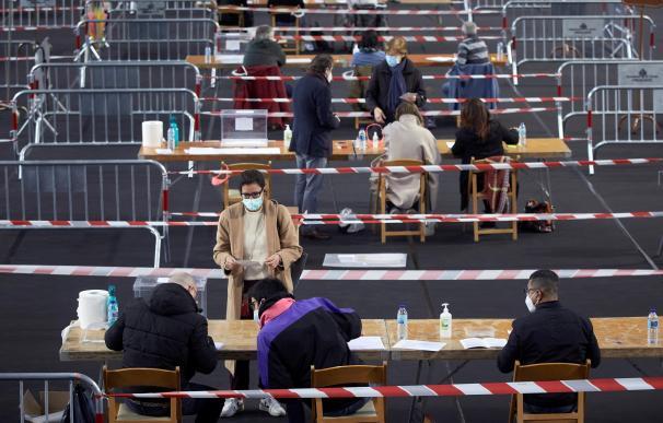 Varias personas votan en el colegio electoral del polideportivo municipal de Palau en Girona a primera hora de este domingo, cuando la mayoría de los 2.763 colegios electorales de Cataluña han abierto pocos minutos después de las 09:00 de esta mañana.