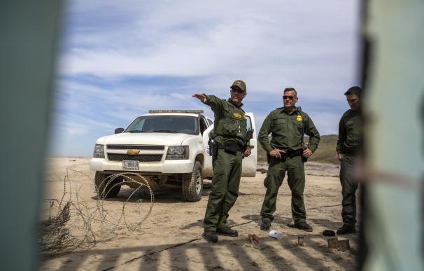 Varios patrulleros fronterizos de Estados Unidos vigilan los trabajos de refuerzo en el muro con México .