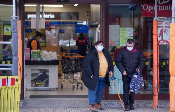 Un hombre y una mujer salen de un supermercado en el municipio gallego de Guitiriz, en Lugo.