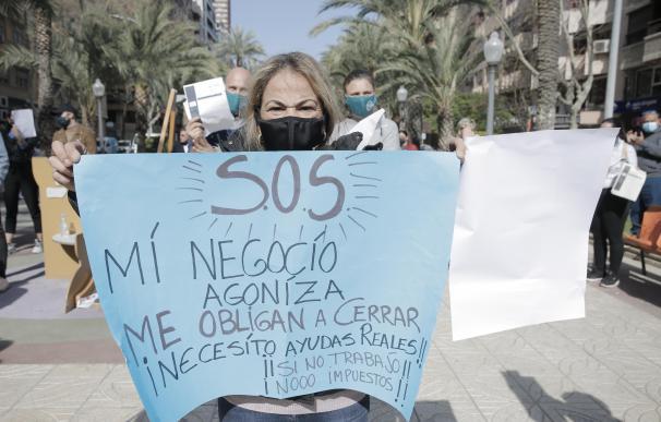 Una mujer perteneciente al sector hostelero de Alicante sostiene una pancarta en una manifestación.
