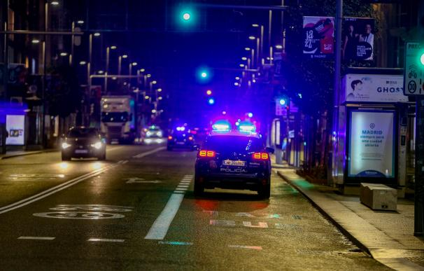 Un coche de Policía Nacional circula durante la primera noche de toque de queda en Madrid.