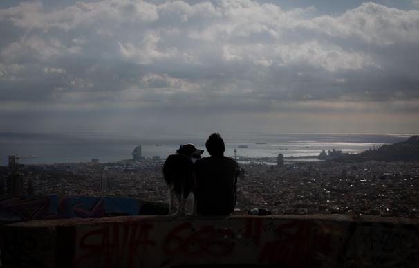 Un joven mira el paisaje en el mirador Turó de la Rovira, en Barcelona.
