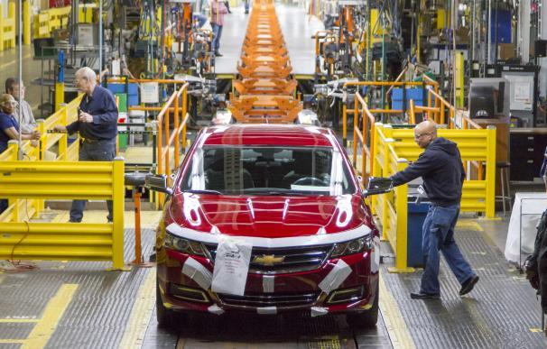 Dos operarios de General Motors trabajan en una planta de Detroit en un modelo Chevrolet.