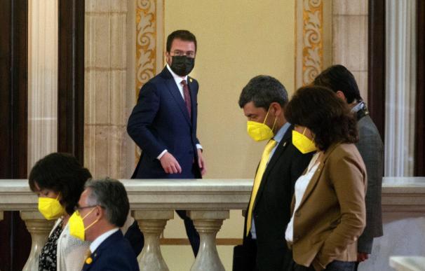 El candidato de ERC, Pere Aragonés, junto a varios diputados de JxCat, en los pasillos del Parlament