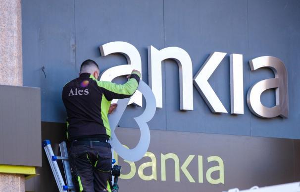 Operarios desmontan el rótulo de Bankia de la sede principal del banco en Logroño este sábado tras iniciar CaixaBank su andadura, una vez culminado el proceso legal de fusión con Bankia.