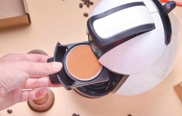 Una persona introduce una cápsula en una cafetera