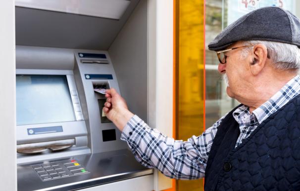 Un jubilado sacando el dinero de la pensión en un cajero del banco.