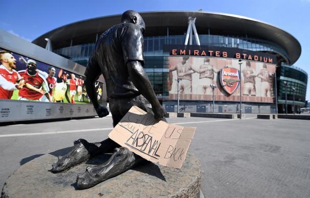 """Un cartel con el mensaje """"Devolvednos a nuestro Arsenal"""" colocado a las puertas del Emirates Stadium del club en Londres (REino Unido) este martes. La Autoridad británica de mercados y competencia (CMA, en inglés) """"examinará cuidadosamente"""" si existen indicios de que el proyecto de Superliga europea de fútbol viola las leyes de competencia en el Reino Unido, indicó este martes un portavoz."""