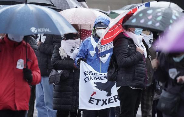 Varias personas se cubren de la lluvia durante una manifestación a favor de la vuelta de los presos de ETA al País Vasco, en Bilbao.
