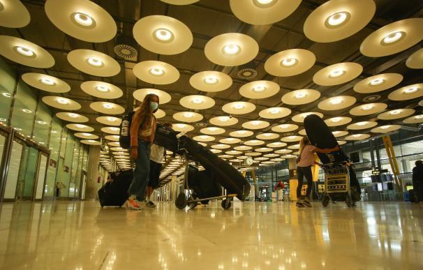 Tres personas transportan su equipaje con carros en la terminal T4 del Aeropuerto Adolfo Suárez Madrid-Barajas, en Madrid (España), a 15 de marzo de 2021. El Gobierno ha prorrogado hasta el próximo 30 de marzo la limitación de los vuelos directos y buques de pasaje entre Reino Unido y los aeropuertos y puertos españoles y los vuelos entre Brasil y la República de Sudáfrica y los aeródromos españoles. La orden, recogida este viernes en el Boletín Oficial del Estado (BOE), fue aprobada en el Consejo de Ministros de este martes y prorroga las órdenes de 22 de diciembre de 2020 y de 2 de febrero de 2021, por los que, respectivamente, el Ejecutivo estableció medidas excepcionales para limitar la propagación y el contagio de las cepas de COVID-19. 15 MARZO 2021;BRASIL;SUDÁFRICA;AEROPUERTO;REINO UNIDO;VUELOS;VIAJES;TURISMO Ricardo Rubio / Europa Press   (Foto de ARCHIVO) 15/3/2021