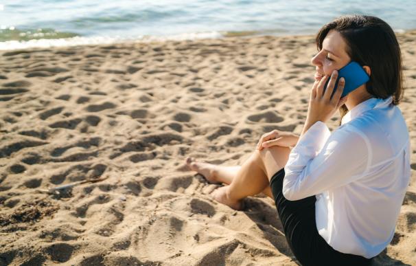 Mujer recibiendo una llamada de trabajo en vacaciones.