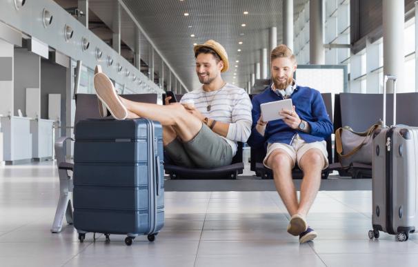 Dos chicos jóvenes en un aeropuerto antes de irse de viaje.