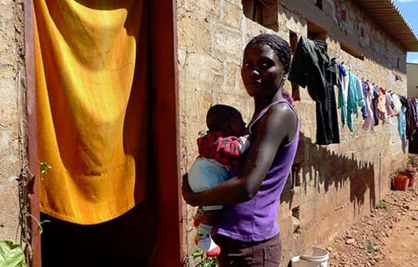 Martha Mumba, que es VIH positiva, sostiene a su hijo de seis semanas en brazos a la puerta de su casa en Lusaka | UNICEF