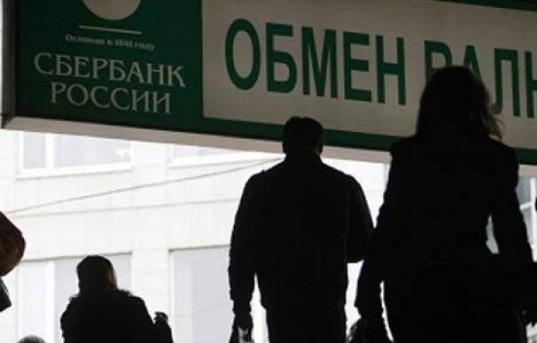 Un grupo de personas pasa por debajo de un anuncio de Sberbank, banco estatal ruso