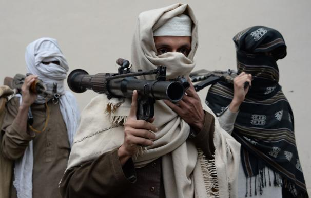 Former Afghan Taliban fighters carry their weapons