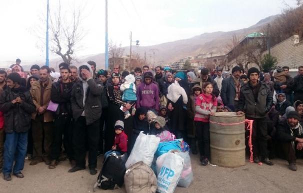 Un grupo de personas esperan la llegada de un convoy de ayuda humanitaria en el pueblo asediado de Madaya