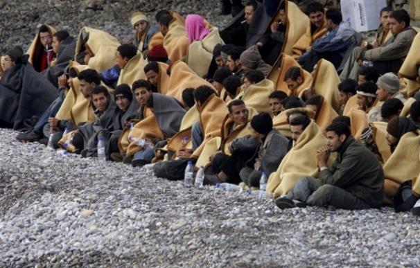 Un grupo de inmigrantes se cubre con mantas a su llegada a la isla de Creta en diciembre de 2007 | Reuters