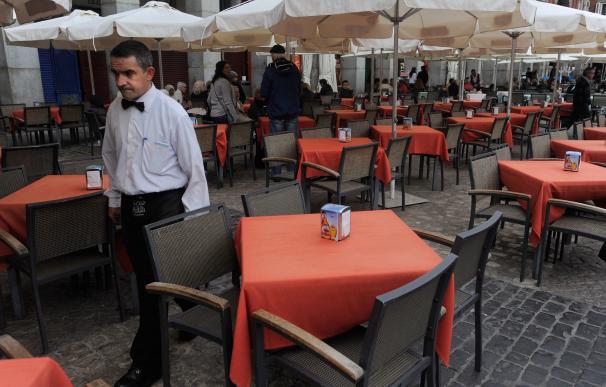 Un camarero anda entre mesas vacías en la Plaza Mayor de Madrid. Getty Images