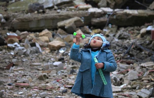 Una niña siria hace pompas de jabón en los escombros de la zona rebelde de Daraa, el 31 de enero de 2017 (MOHAMAD ABAZEED / AFP)