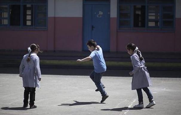 Unos niños juegan en el patio de un colegio.