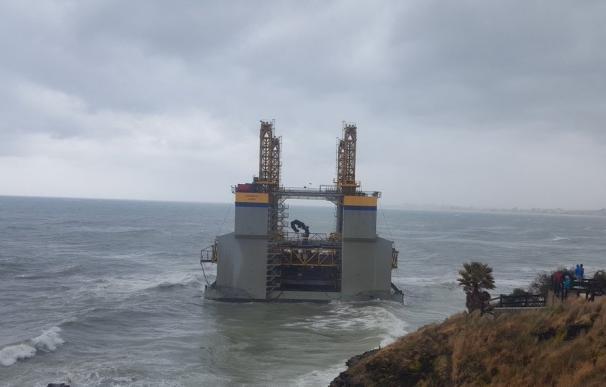 Numerosas personas se acercan a contemplar la estructura marítima varada en una playa de Benalmádena