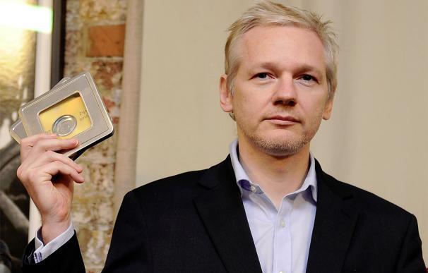 El fundador de WikiLeaks, Julian Assange, sostiene los CD con datos sobre dos mil clientes de bancos suizos entregados por el ex banquero Rudolf Elmer.