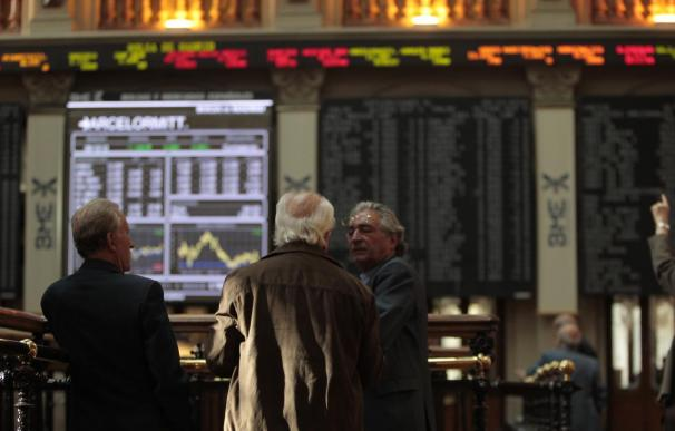 Un grupo de inversores comentan la sesión sobre el parqué de la Bolsa de Madrid.