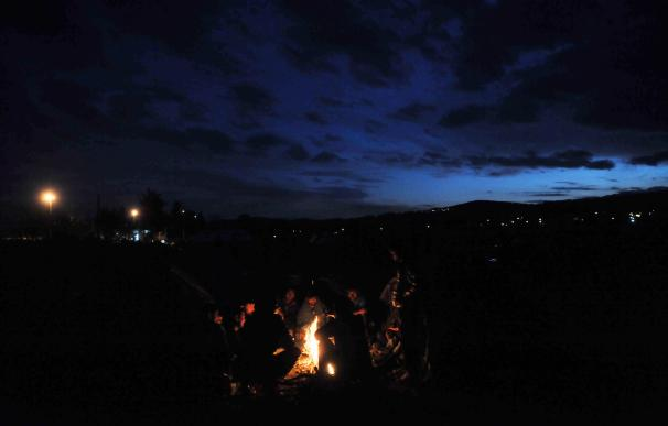 Migrant and refugees keep warm around a bonfire as