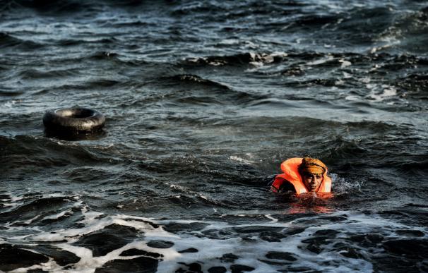 Un hombre nada en hacia la costa en frente de la isla de Lesbos/ AFP