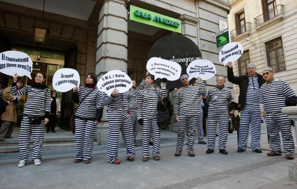 12 Personas vestidas de presos protestan por la llegada de Rato a Caja Madrid