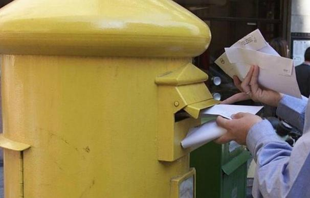 Una persona echa varias cartas a un buzón de Correos. EFE