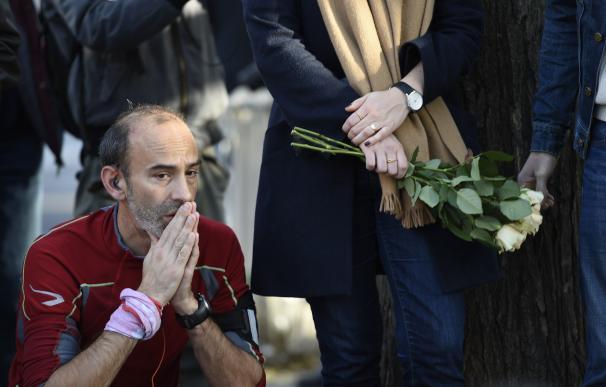 People mourn near the crime scene of the Bataclan