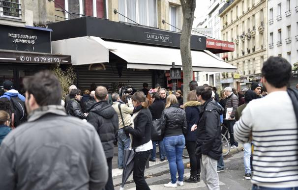 People stand outside the cafe 'La Belle Equipe' at