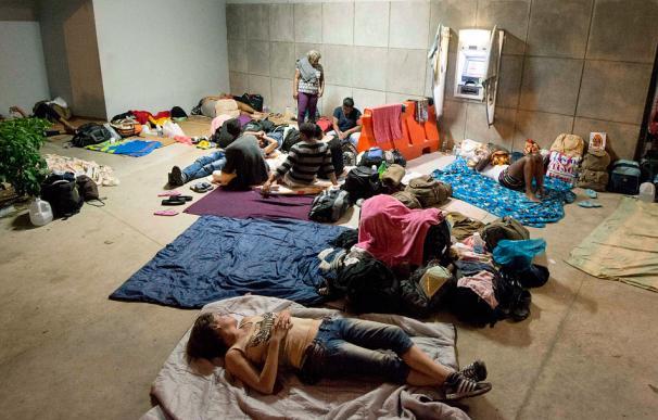 Cubanos descansando en la oficina migratoria de Penas Blancas en la frontera de Costa Rica y Nicaragua (EZEQUIEL BECERRA / AFP)
