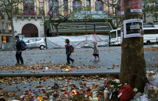 Children walk past the Bataclan Theater in Paris o