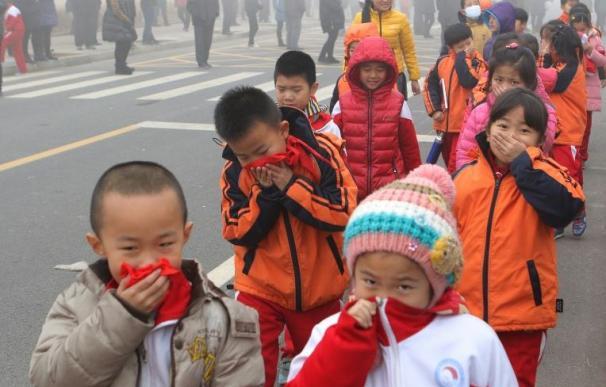 Unos niños caminan tapándose la boca para no respirar aire contaminado/AFP