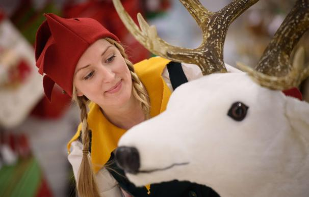 A Christmas elf poses with a toy reindeer during a