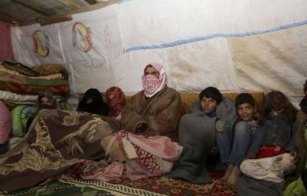 Una familia tirita de frío en el interior de una tienda en un campo de refugiados /AFP