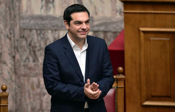 Greek Prime Minister Alexis Tsipras applauds the p