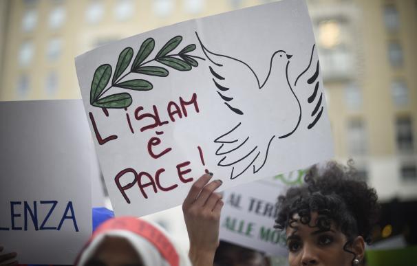 """Un mujer musulmana muestra un cartel en donde se dice """"Islam es paz""""."""