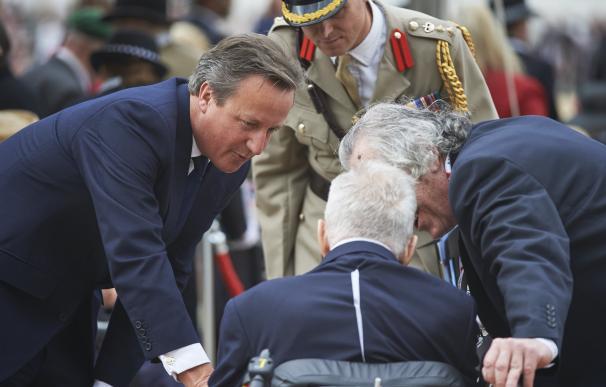British Prime minister David Cameron (L) speaks to
