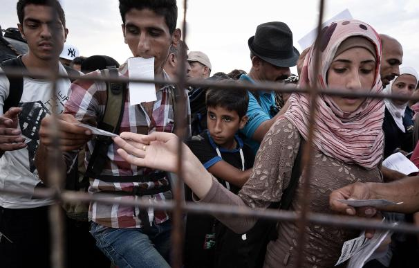 Syrian refugee hands over tickets prior to boardin
