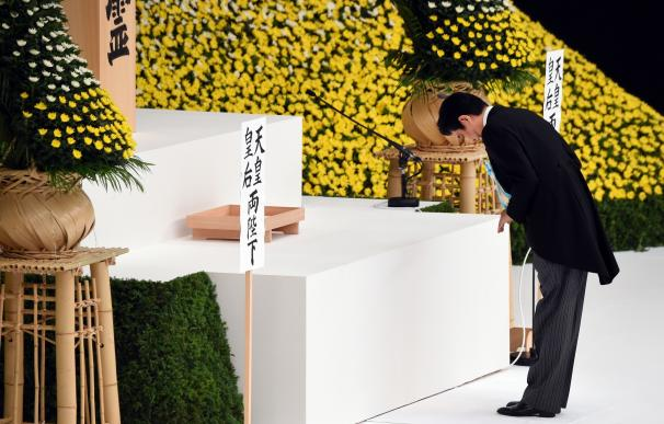 Japan's Prime Minister Shinzo Abe bows before plac