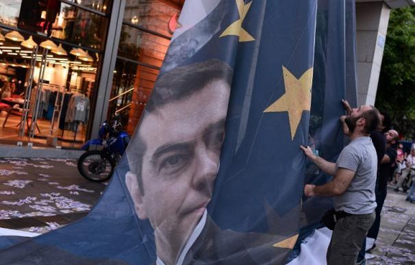 Retirada de una bandera de la UE con la imagen de Tsipras