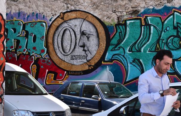 Un hombre camina delante de un graffiti que pone '0 euros' en Atenas
