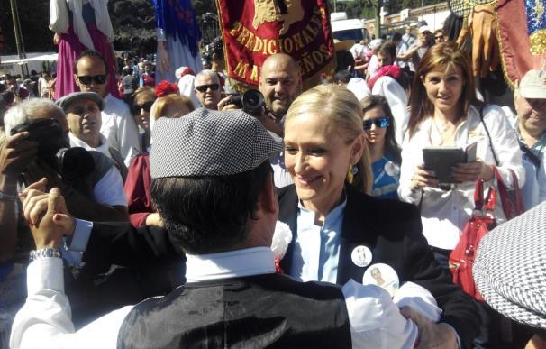 Cifuentes baila un chotis, compra rosquillas y pide trabajo al Santo en un paseo marcado por peticiones electorales
